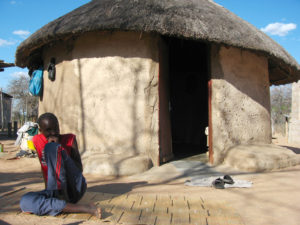 A boy in front of his grandmother's hut