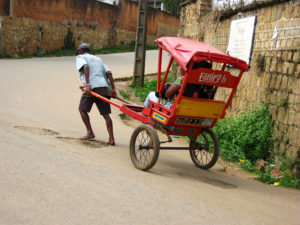 "A typical ""posy-posy"" driver struggling barefoot uphill to carry his passengers."