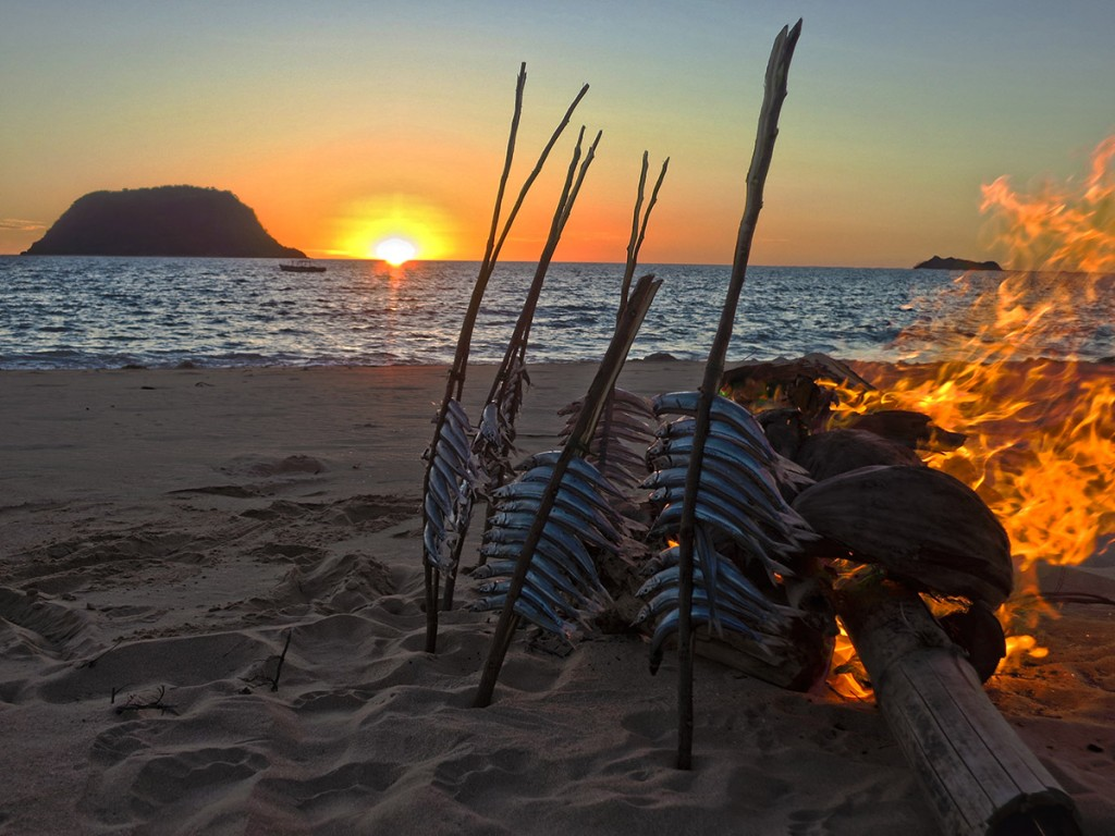 """Smoking fish on our village's beach at sunset. These small fish were caught from the women's style of netfishing, called """"magnaroba""""."""