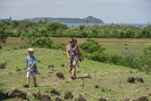 Lora carrying David and walking with Matimu to visit with people in another village on Nosy Mitsio.