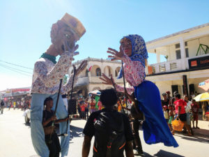 "Giant Antakarana ""marionettes"" leading the parade for Independence Day along the main street of Ambilobe."