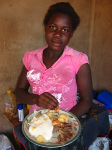 A girl eating typical Shangaan food