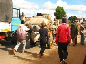 A few guys hauling a big load of charcoal along the road.