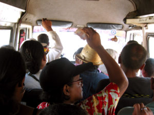 "A standard ""taxi be"" (public transport van) in Madagascar. People are passing their money back to pay the driver... the standard fee is $.15 anywhere along the taxi be route."