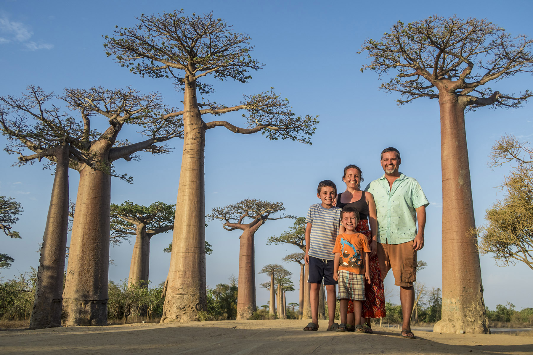 """A family photo at the """"Avenue of Baobabs"""" at sunset."""
